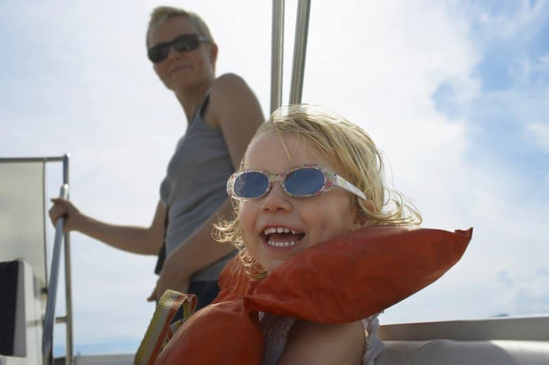 Young girl smiling with sunglasses and Mom that trust each other on yacht